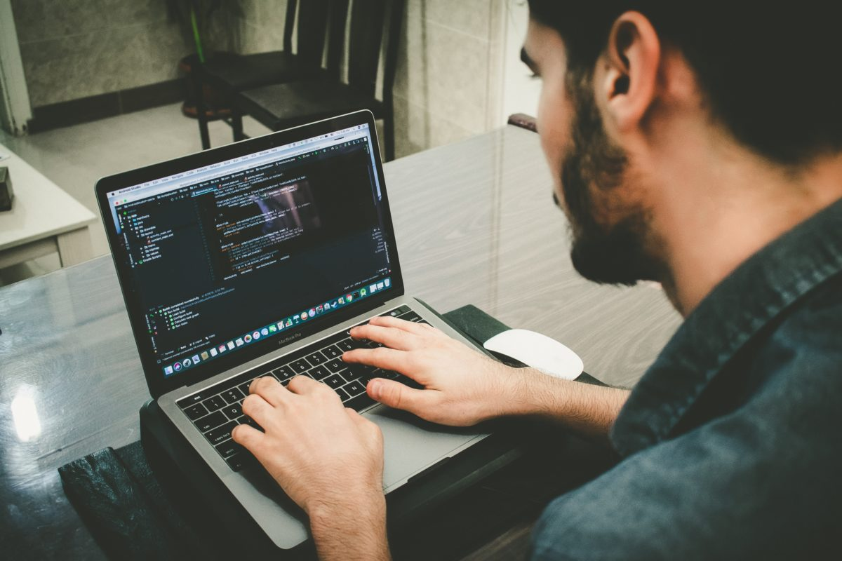 an IT specialist works coding on his laptop